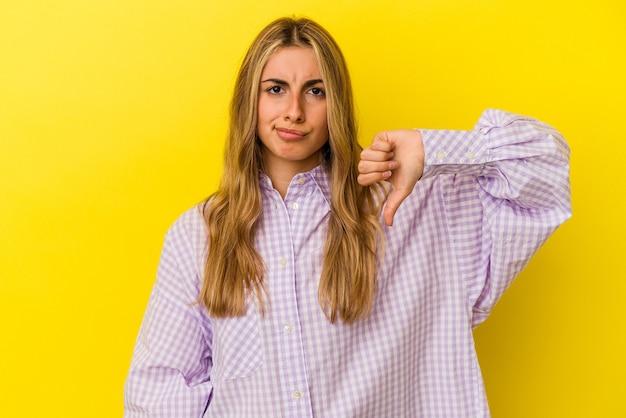 젊은 금발 백인 여자 아래로, 실망 개념 엄지를 보여주는 노란색 배경에 고립.