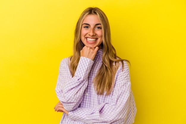 행복 하 고 자신감, 손으로 턱을 만지고 웃 고 노란색 배경에 고립 된 젊은 금발의 백인 여자.