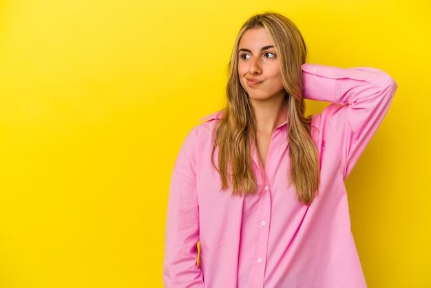 Молодая белокурая кавказская женщина изолирована на желтом фоне, касаясь затылка, думая и делая выбор.