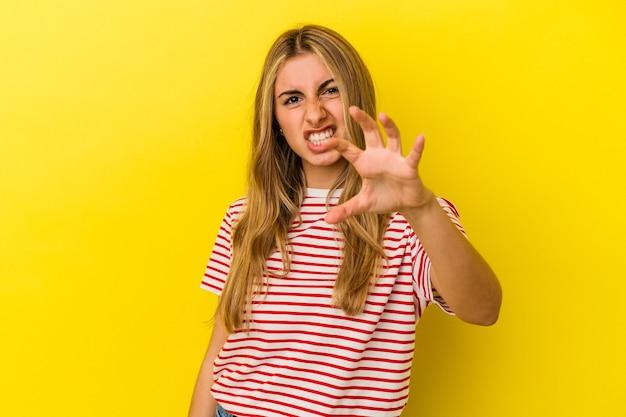 猫を模倣した爪、攻撃的なジェスチャーを示す黄色の壁に分離された若い金髪白人女性