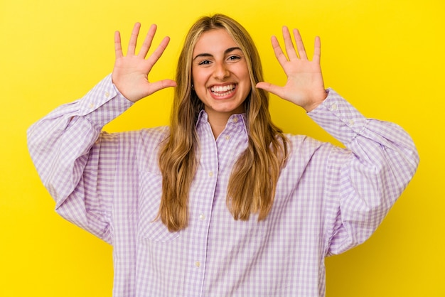黄色の壁に孤立した若い金髪の白人女性は、手で10番を示しています。