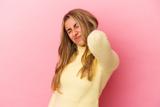 Young blonde caucasian woman isolated on pink background having a neck pain due to stress, massaging and touching it with hand.