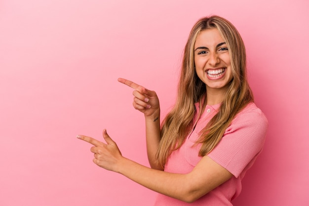 Young blonde caucasian woman isolated on pink background pointing with forefingers to a copy space, expressing excitement and desire.
