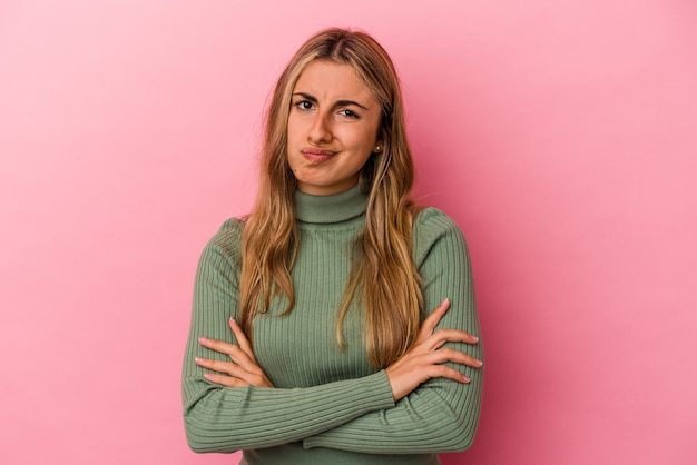 Young blonde caucasian woman isolated on pink background unhappy looking in camera with sarcastic expression.
