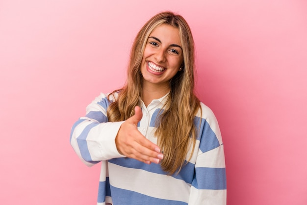 Young blonde caucasian woman isolated on pink wall stretching hand at front in greeting gesture