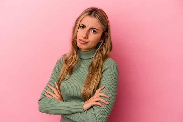 Young blonde caucasian woman isolated on pink wall suspicious, uncertain, examining you.