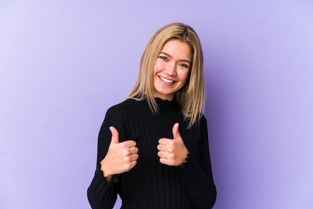 若い金髪白人女性は両方の親指を上げて、笑顔で自信を持って分離しました。