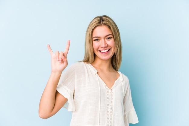 革命の概念として角ジェスチャーを示す分離された若い金髪白人女性。