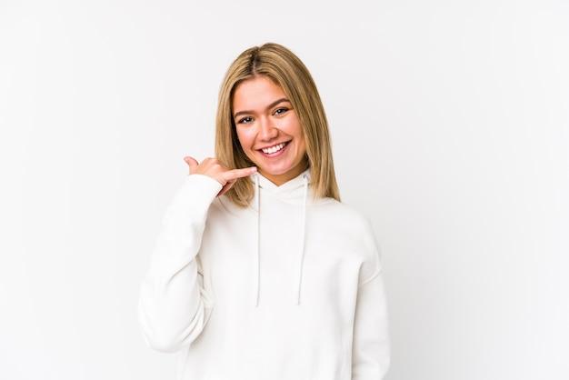 分離された若い金髪白人女性の指で携帯電話の呼び出しジェスチャーを示します。