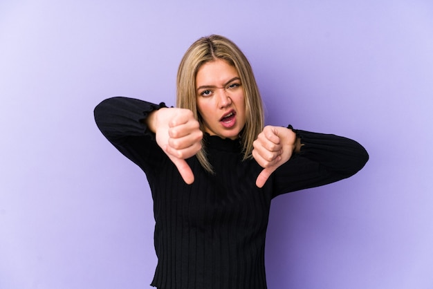 Young blonde caucasian woman isolated showing thumb down and expressing dislike.