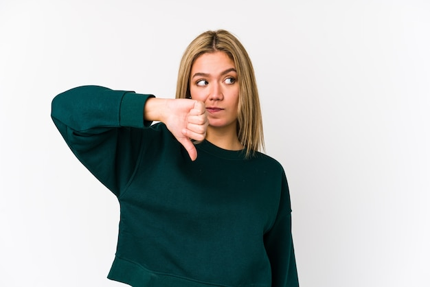 Young blonde caucasian woman isolated showing thumb down