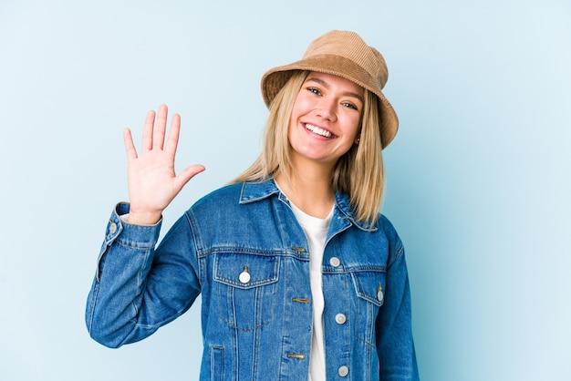 若い金髪白人女性は指で陽気な表示数5を笑顔を分離しました。