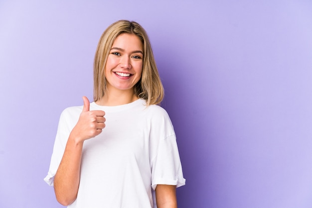 Young blonde caucasian woman isolated smiling and raising thumb up