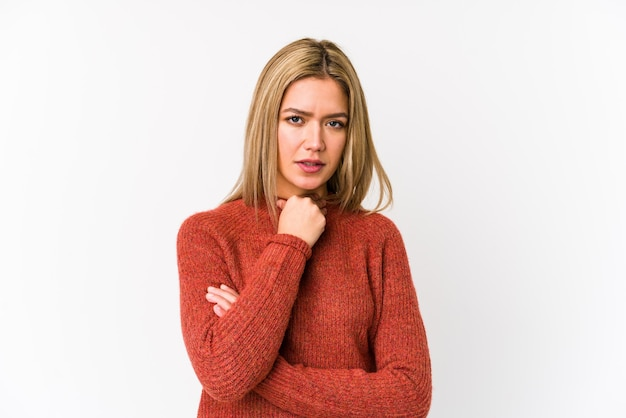 分離された若い金髪白人女性は、ウイルスや感染症のために喉の痛みに苦しんでいます。