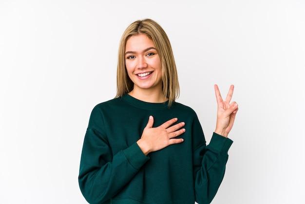 Молодая белокурая кавказская женщина изолировала принимать присягу, кладя руку на комод.