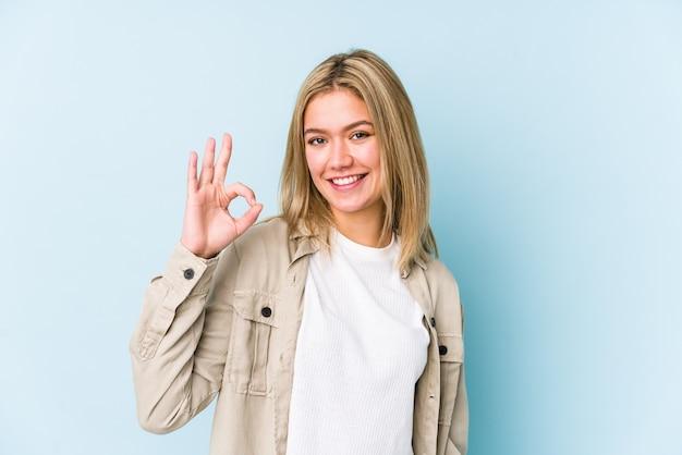 分離された若い金髪白人女性は目をウインクし、手でいいジェスチャーを保持しています。