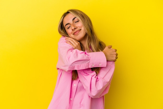 Young blonde caucasian woman isolated on yellow background hugs, smiling carefree and happy.