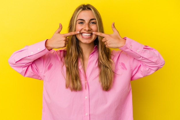 Young blonde caucasian woman isolated on yellow background smiles, pointing fingers at mouth.