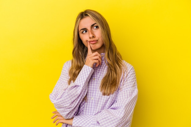 Young blonde caucasian woman isolated on yellow wall contemplating, planning a strategy, thinking about the way of a business