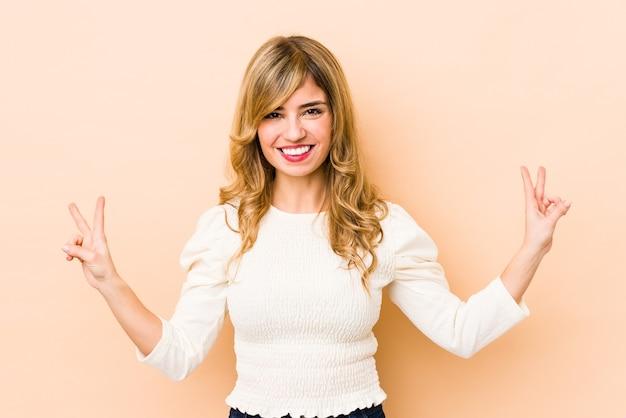 Молодая белокурая кавказская женщина показывает знак победы и широко улыбается.