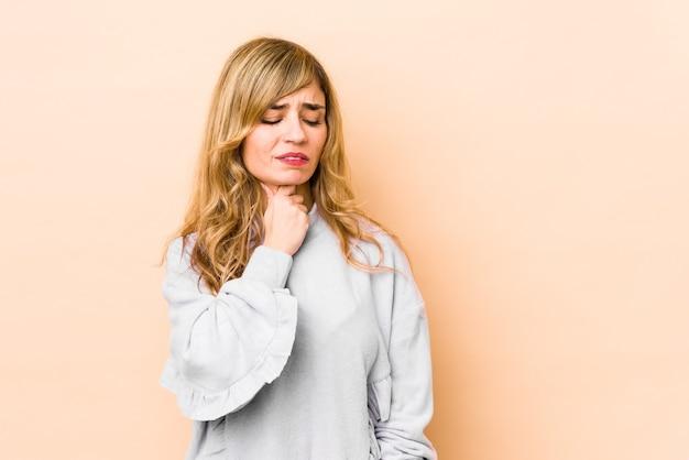 Молодая белокурая кавказская женщина страдает от боли в горле из-за вируса или инфекции.