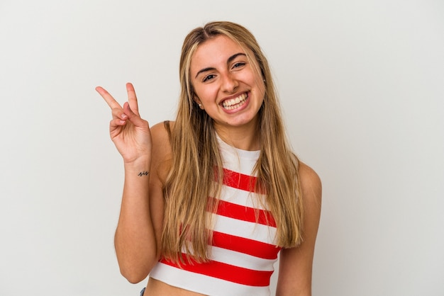 Young blonde caucasian woman on white background isolated joyful and carefree showing a peace symbol with fingers.