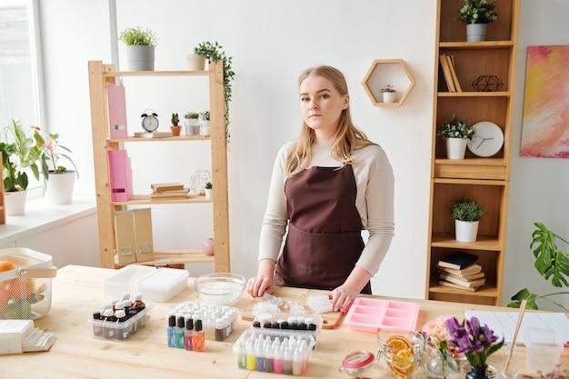 手作り石鹸を作りに行く間スタジオのテーブルのそばに立っている茶色のエプロンで若い金髪」に写っていた
