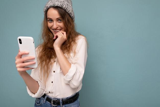 カジュアルな白いシャツと灰色の帽子を身に着けている若い金髪の巻き毛の女性