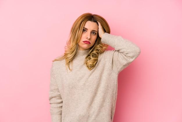 ショックを受けて孤立したセーターを着ている若いブロンドのかわいい女性、彼女は重要な会議を思い出しました。