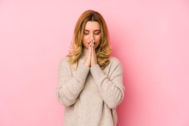 口の近くで祈って分離された手をつないでセーターを着ている若い金髪のかわいい女性は自信を持っています。
