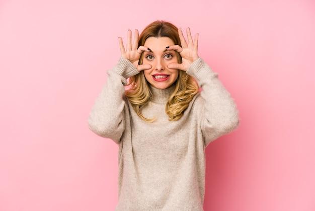 Молодая белокурая милая женщина в изолированном свитере держит глаза открытыми, чтобы найти возможность для успеха.