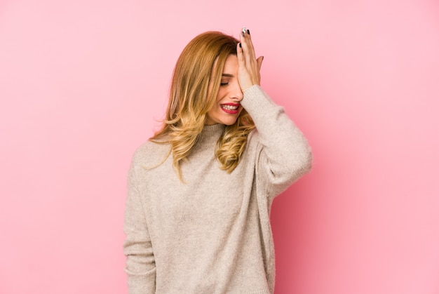 Young blonde cute woman wearing a sweater forgetting something, slapping forehead with palm and closing eyes.