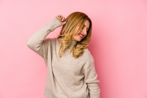 Young blonde cute woman wearing a sweater isolated dancing and having fun.