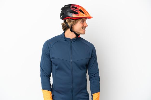 Молодой блондин велосипедист человек изолирован на белом фоне смотрит сторону