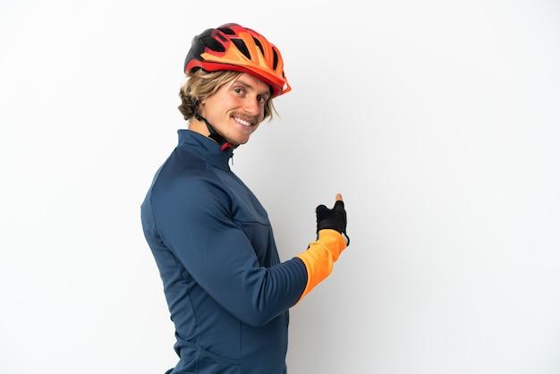 Молодой блондин велосипедист человек изолирован на белом фоне, указывая назад