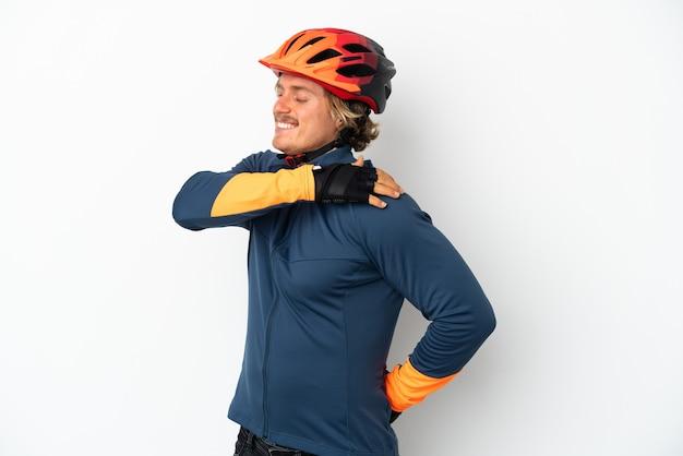 努力したために肩の痛みに苦しんでいる白い背景で隔離の若い金髪のサイクリストの男
