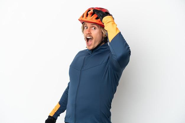 横を見ながら驚きのジェスチャーをしている白で隔離の若い金髪のサイクリストの男