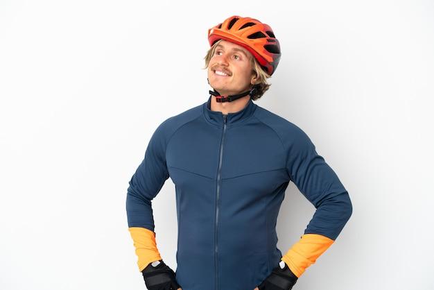 찾는 동안 아이디어를 생각하는 흰 벽에 고립 된 젊은 금발의 사이클 남자