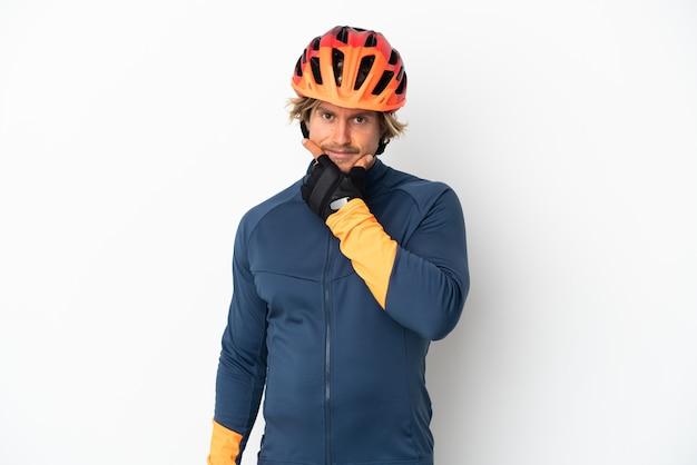 思考の白い壁に孤立した若い金髪サイクリストの男