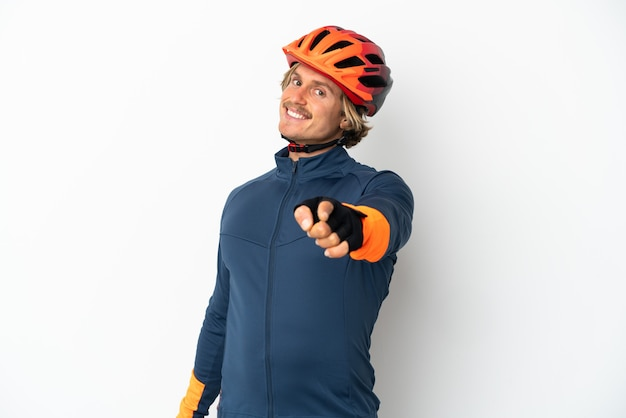 Young blonde cyclist man isolated on white background pointing front with happy expression