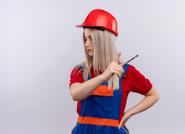 Молодая блондинка инженер-строитель девушка в униформе держит ручку и указывает на правую сторону с другой рукой на талии, глядя на левую сторону на изолированной белой стене с копией пространства