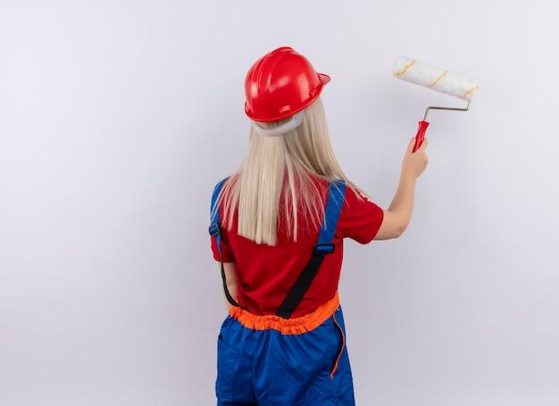 Giovane ragazza bionda del costruttore dell'ingegnere nella parete della pittura uniforme con il rullo di vernice che sta dietro la vista sulla parete bianca isolata con lo spazio della copia