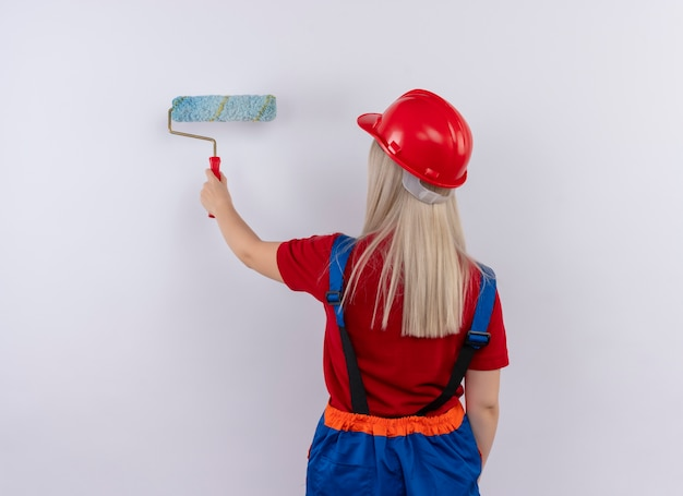 Young blonde engineer builder girl in uniform painting wall with paint roller standing in behind view on isolated white wall