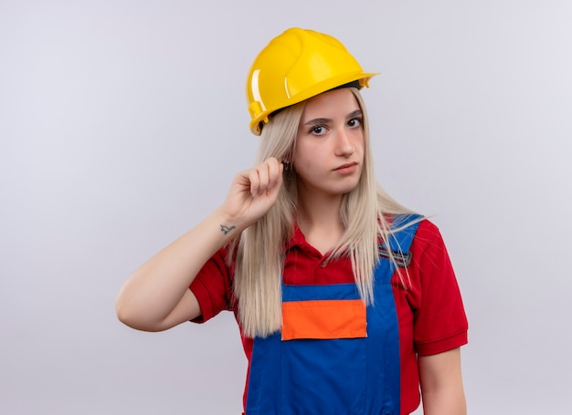 Young blonde engineer builder girl in uniform putting finger on ear looking  on isolated white wall