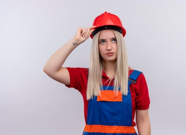 Giovane ragazza bionda del costruttore dell'ingegnere in uniforme che mette la mano sulla testa che osserva in su sulla parete bianca isolata