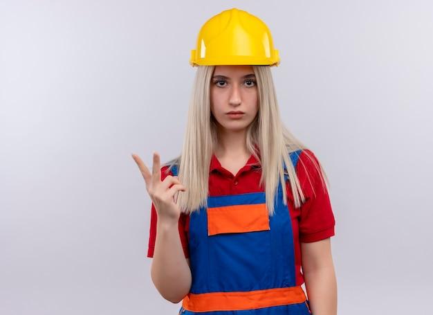 Giovane ragazza bionda del costruttore dell'ingegnere in uniforme che mostra due alla ricerca sulla parete bianca isolata con lo spazio della copia