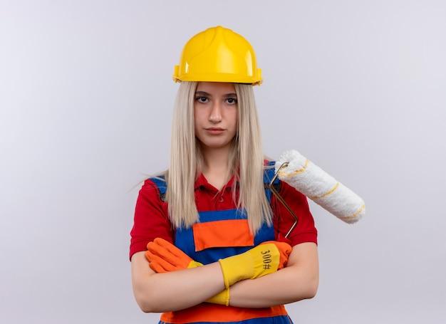 Giovane ragazza bionda del costruttore dell'ingegnere in guanti d'uso uniformi che tengono il rullo di vernice che sta nella posizione chiusa che osserva sulla parete bianca isolata con lo spazio della copia