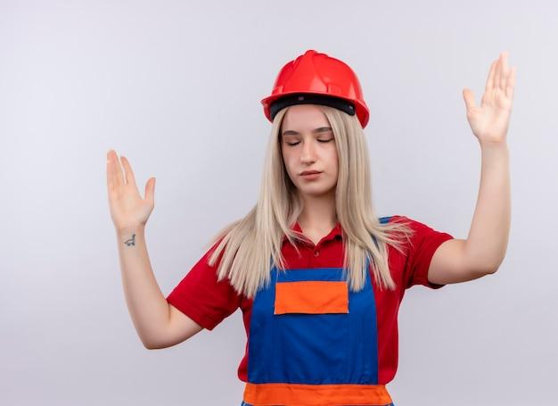 Giovane ragazza bionda del costruttore dell'ingegnere in uniforme con le mani alzate e gli occhi chiusi sulla parete bianca isolata