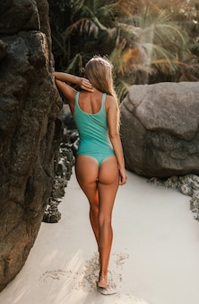 Young blonde european woman in bikini swimsuit on beach against stone rocks stands backwards
