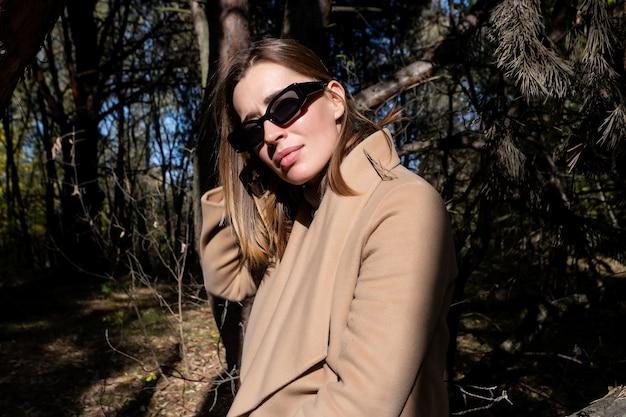 가을 공원에서 산책하는 젊은 금발 패션 여성 클래식 베이지색 코트와 검은 스카프에 세련된 여성 모델